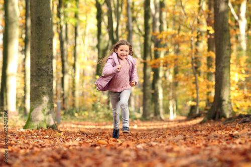 Valokuva  Kleines Mädchen rennt durch einen herbstlichen Wald
