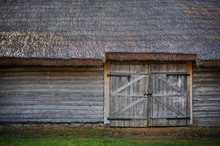 Old Wooden Barn. Log Wall, Gate And Thatched Roof.