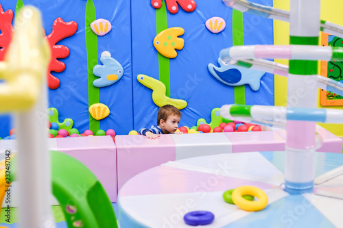 Happy boy having fun in ball pit in kids amusement park and indoor play center. Child playing with colorful balls in playground