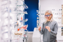 Woman Looking At Glasses At Optic Store.