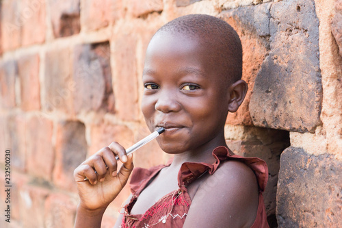 Fényképezés  An 11-year old Ugandan girl smiling, holding a pen against her mouth and leaning