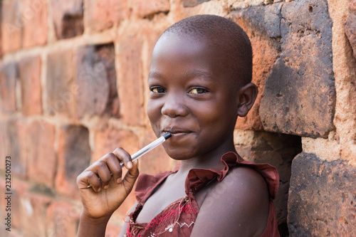Vászonkép  An 11-year old Ugandan girl smiling, holding a pen against her mouth and leaning