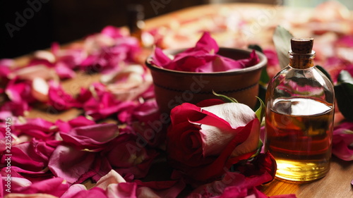 Poster Spa Clay bowl and aroma oil glass bottle among roses petals on the wooden table, natural raw material, selected focus