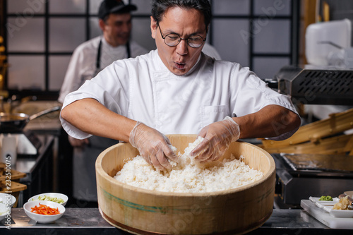 Fototapeta young emotional man is happy to prepare rice. funny chef is singing songs while cooking rice for sushi. close up photo obraz