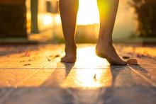 Barefoot Man Walking On The Floor With Sunrise Light Shine