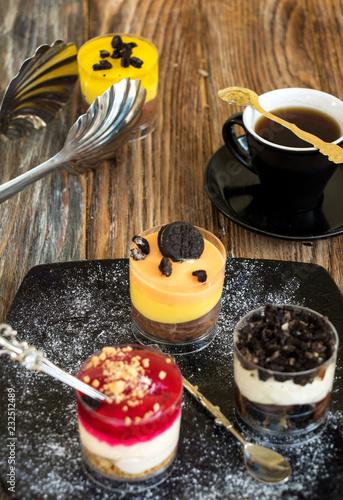 Poster Snoepjes Vier verschiedene kleine Nachtische im Glas mit einer Tasse Mokka