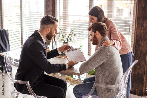 Photo Young caucasian couple consulting with bank financial adviser before buying new house