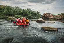 Group Of Men And Women, Enjoy Water Rafting Activity At River. Rafting Family On Holidays