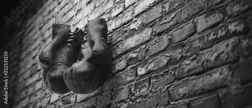 Photo Old boxing gloves hang on nail on brick wall with copy space for text