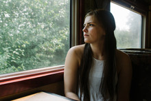 Teenage Passenger Looks Out Train Car Window At Scenery
