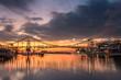 Dramatischer Sonnuntergang hinter einer Brücke am Wasser