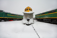 Snowplow Train Or Snow Removal Train With Railroad Snow Removal Equipment For Cleaning Tracks Ans Rails From Snow Stays On The Station With Other Locomotives In Cold Winter Day