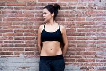 Athletic Sportswoman In Sportsbra Over Brick Wall.