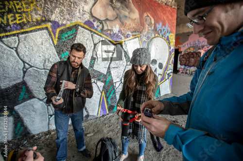 Friends passing out headlamps in front of graffiti-covered wall, Portland, Maine, USA