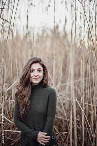 Smiling young woman standing in long grass, Peaks Island, Maine, USA