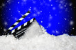 canvas print picture - Frozen film clapper / clapperboard on blue background with falling snow with copy space