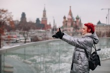 Girl Walking By The Flying Bridge Over Moscow River And Taking Pictures With Her Phone