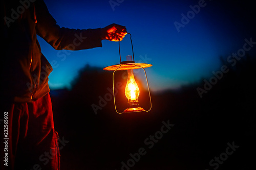 Fotografie, Obraz  hand holds a large old lamp in the dark