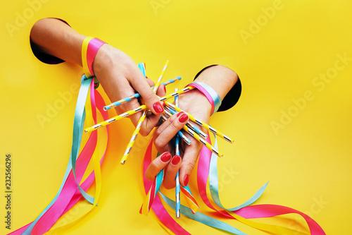 Cukierkowy manicure w stylu pin up. Dłonie z pomalowanymi paznokciami, udekorowane kolorowymi wstążkami na żółtym tle.
