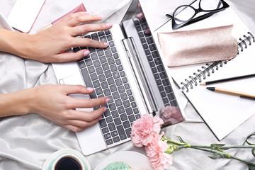 Kobieta pracuje on line. Kobieta pisze na komputerze leżąc na łóżku.