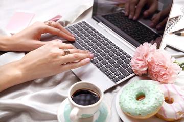 Praca on line. Kobieta pisze na komputerze leżąc na łóżku.