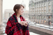Young Woman Having Tea With View On Snowy City