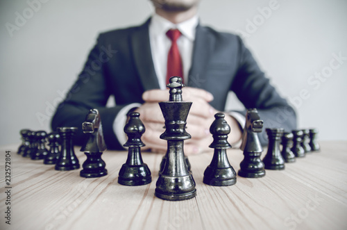 Stampa su Tela Retro style image of a businessman with clasped hands planning strategy with chess figures on an old wooden table