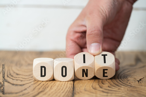 Photo  Hand turns two cubes, changing the word do it to done