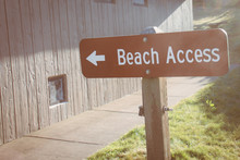 Sign Showing The Way To Beach Access. Sunflare, Taken During Golden Hour.  Filter Applied To Photo