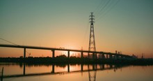 The Sun Starting To Rise/set Behind Melbourne's Westgate Bridge With Traffic Crossing.