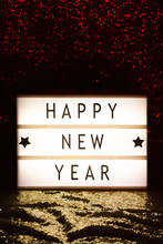 Happy New Year Written On A Lightbox Placed In A Glittery Setting