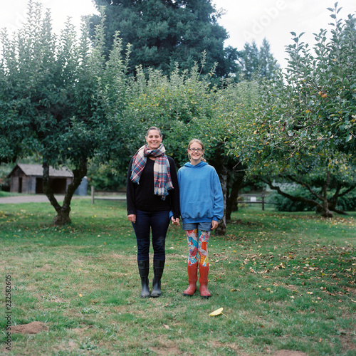 Mother and daughter stand in an apple orchard