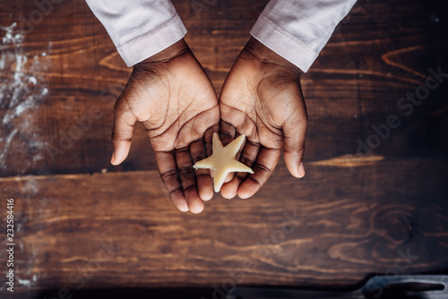 Tuinposter Koekjes Black girl's hands holding a star shaped cookie dough