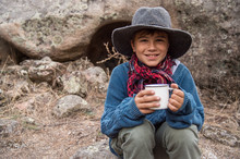 Child With A Hat And A Checkered Scarf Holding A Cup And Sitting On A Stone