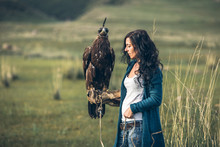 Female Beauty With Golden Eagle Sitting On Her Arm