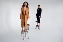 Couple Standing On Chairs