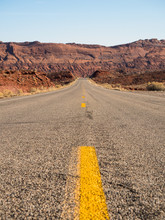 Long Paved Road With Yellow Line Running Through The Southwestern United States.