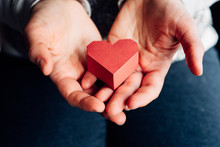 Woman's Hands Holding A Red Paper Heart