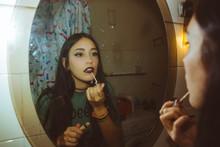 Brunette Girl Putting Lipstick In Bathroom