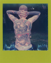 Polaroid Scan Of A Heavily Tattooed Man Sitting Outside.