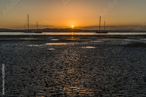 Spoed Foto op Canvas Zee zonsondergang View of a tropical beach during sunset, sailing ships and beautiful reflections