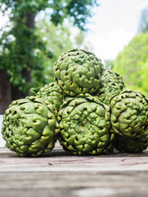 Large Artichokes On A Wooden Background