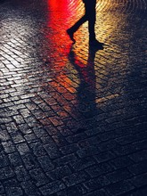 Unrecognizable Person Walking On Asphalt By Night