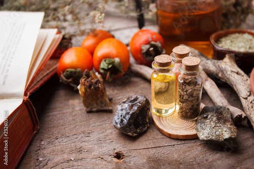 set of bottles, assortment of dry healthy herbs, old books