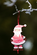 A Santa Claus Xmas Decoration Hanging From A Tree Outdoors