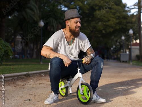 Man on child bicycle in park