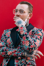 Tattooed Handsome Man With Colourful Flower Jacket Over Red Background