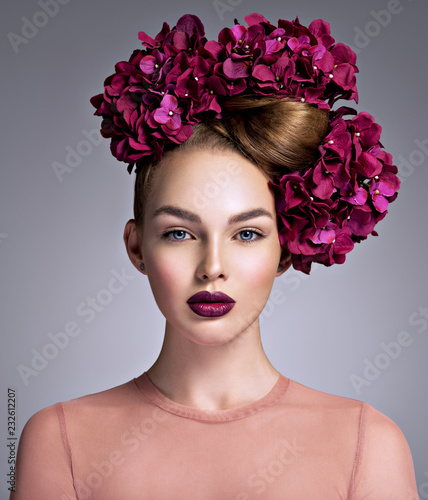 Young woman with a bouquet of purple flowers in her hair.