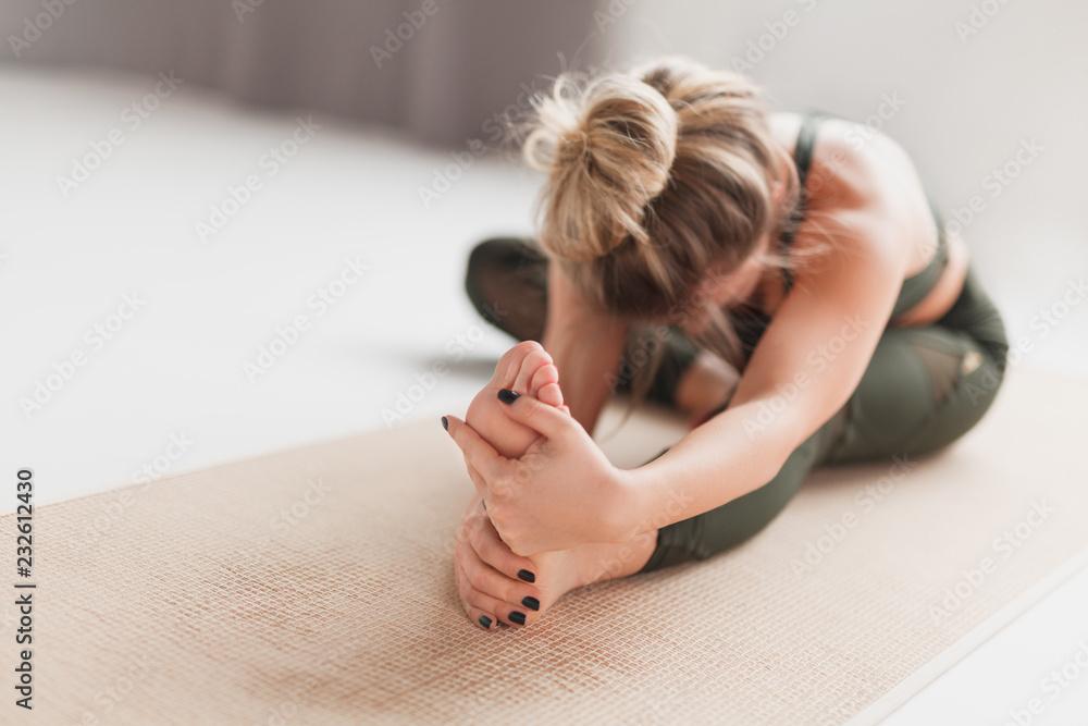 Fotografia Young woman performing Janusirsasana exercise