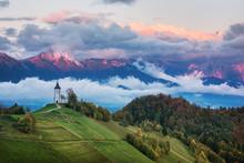 Beautiful Sunrise Landscape Of Church Jamnik In Slovenia With Cloudy Sky